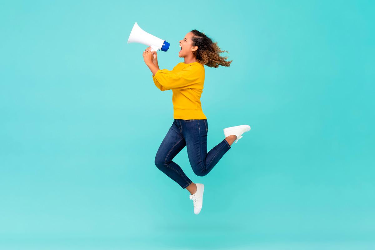 Donna che salta con un megafono in mano